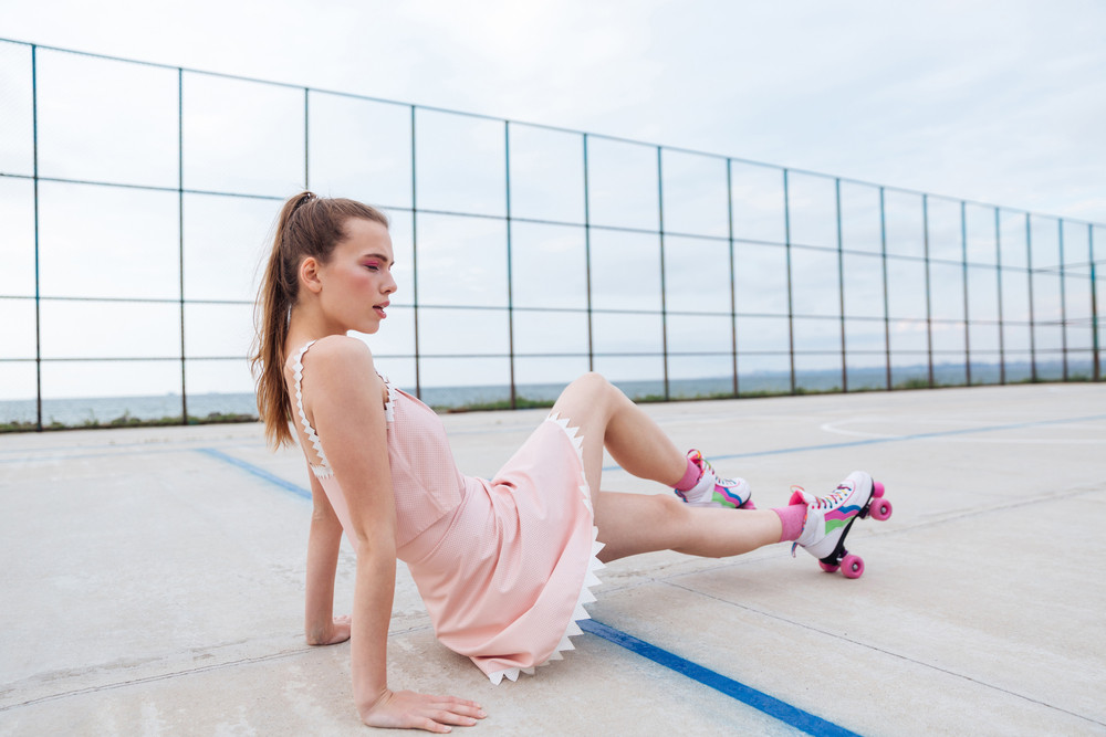 Young beautiful woman on roller skates posing on the playgroud