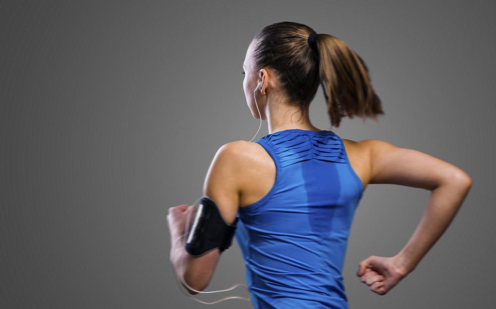 Young beautiful woman running. Studio shot on gray background.