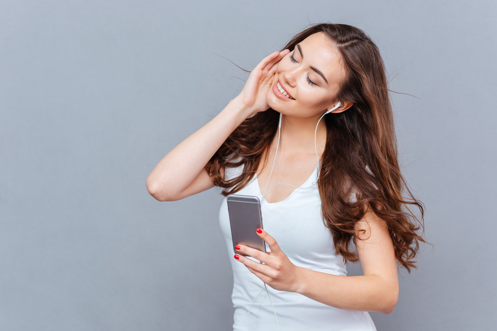 Young beautiful woman using smartphone and listening to music isolated on a gray background