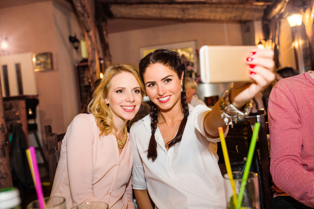 Young beautiful women with cocktails in bar or club taking selfie, having fun