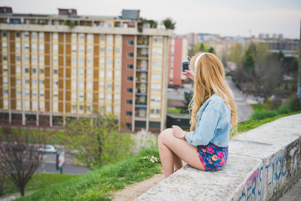 Young blonde caucasian girl listening music with headphones in the suburbs - technology, music, relax concept