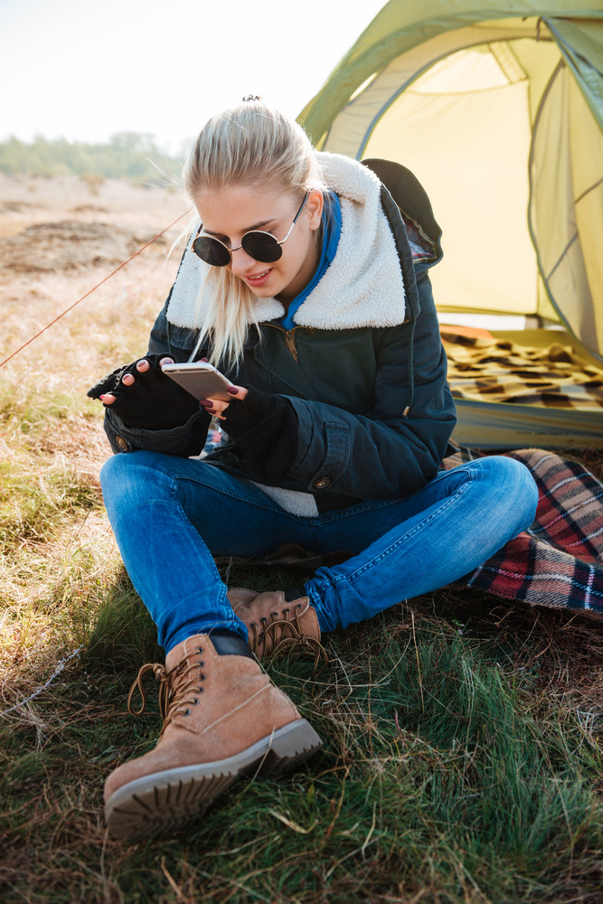Young blonde woman in sunglasses using mobile phone while sitting at her tent