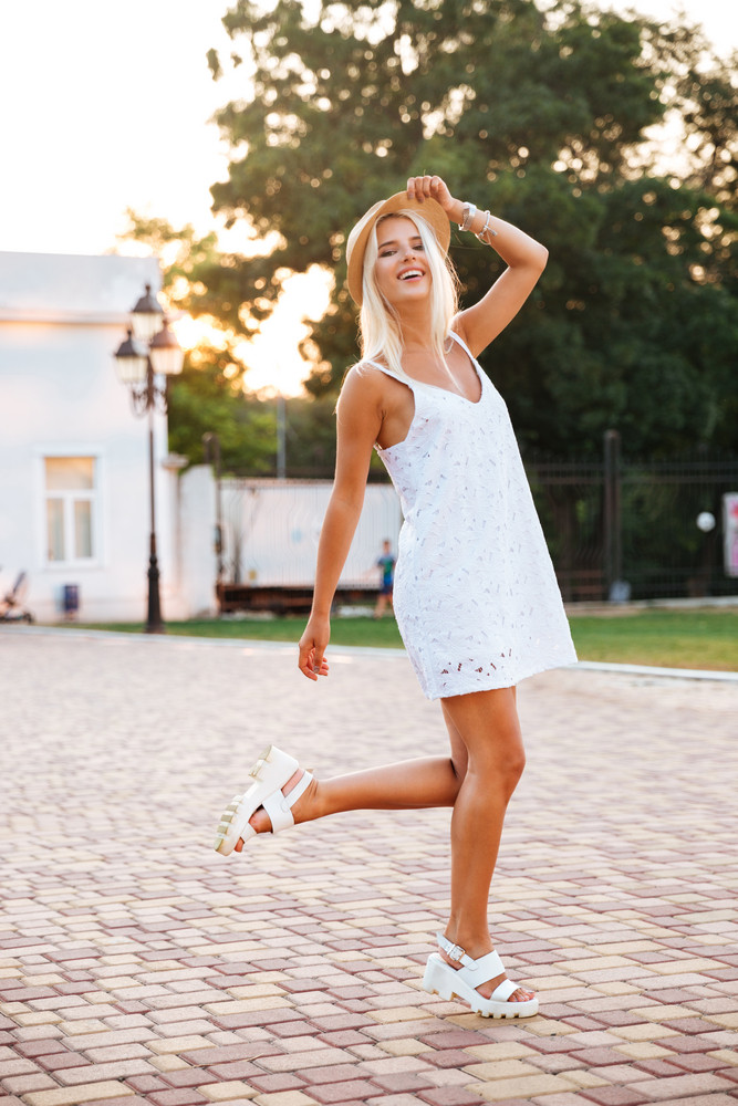 Young blonde woman wearing white dress and hat posing outdoors at the park