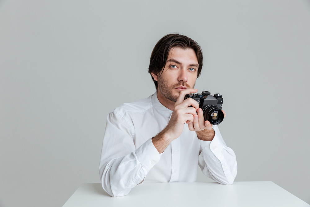 Young bristled man ready to make a photo with camera while sitting at the table isolated on the gray background