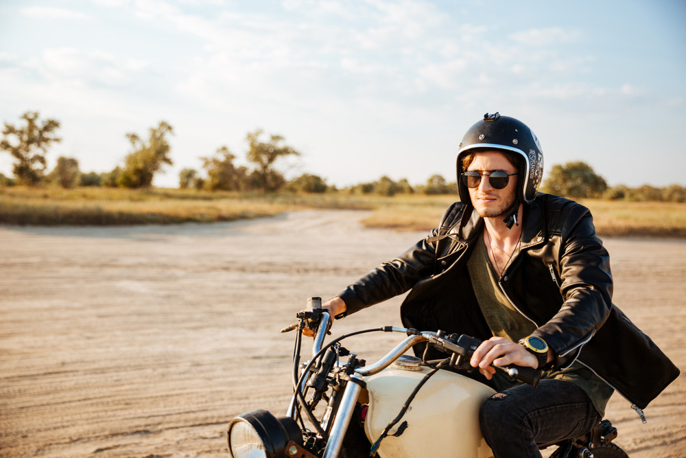 e030bb858f7 Young brutal man in a black jacket and glasses driving retro motorcycle