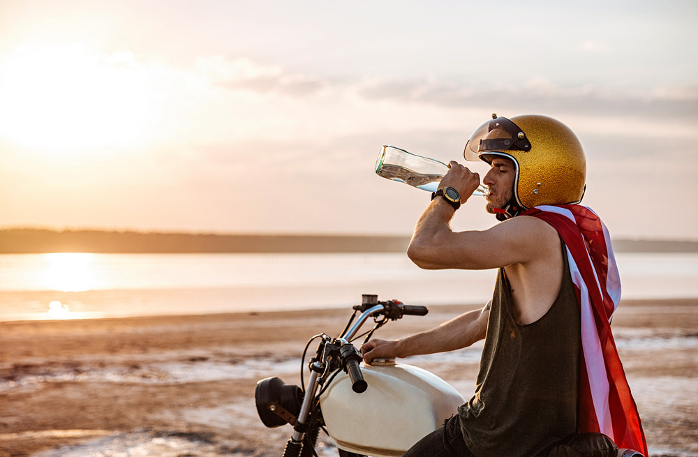 Young brutal man in golden helmet and american flag cape drinking and sitting on his motocycle