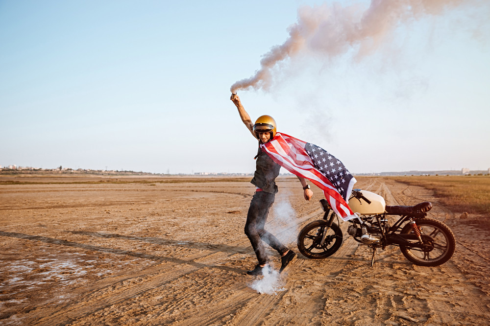 Young brutal man wearing american flag cape and golden helmet holding smoke bomb at the desert