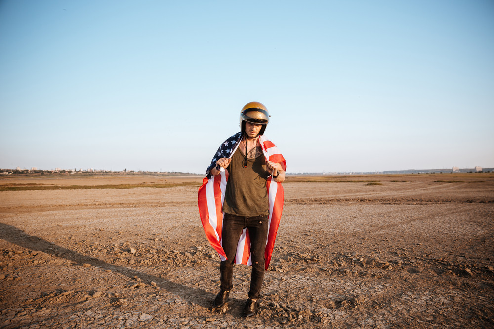 Young brutal man wearing american flag cape and golden helmet posing at the desert