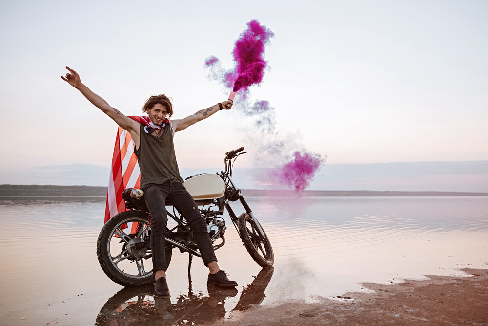 Young brutal man wearing american flag cape holding smoke bomb