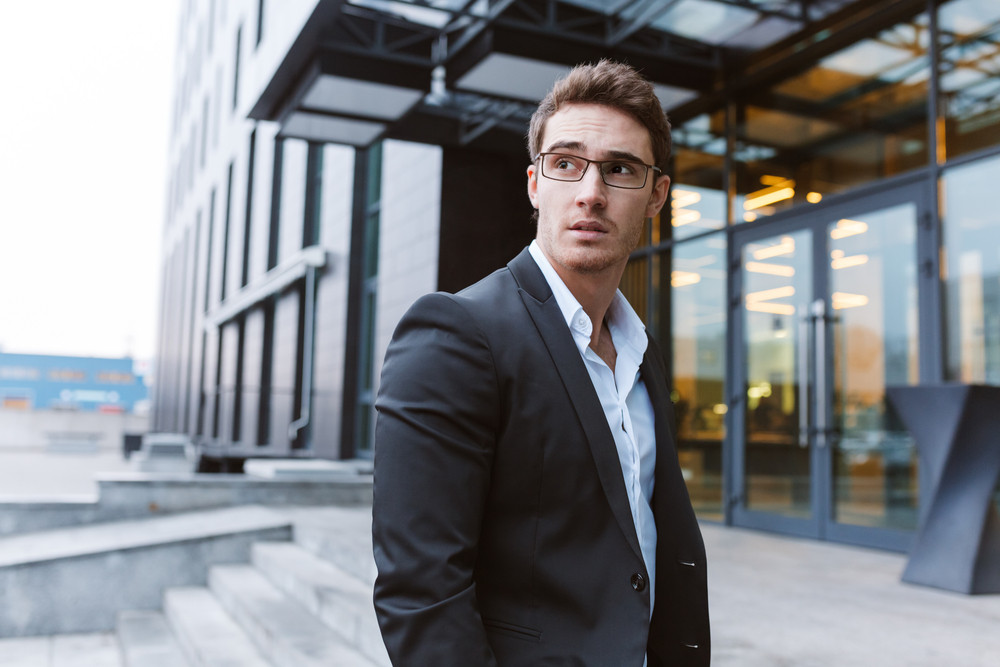 Young Business man in suit and glasses standing near the office. Side view
