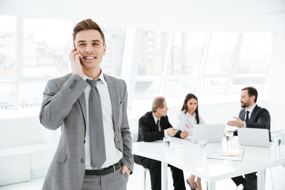 young business man talking at phone in office with colleagues by the