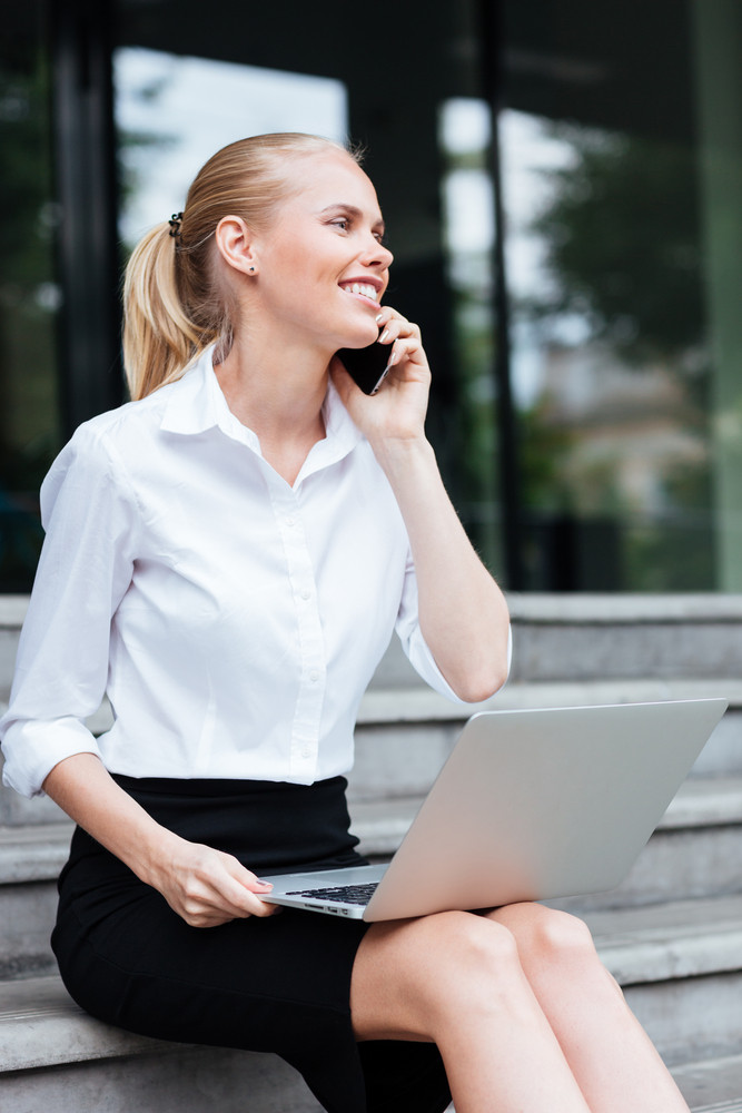 Young business woman sitting on stairs and talking on cell phone outdoors