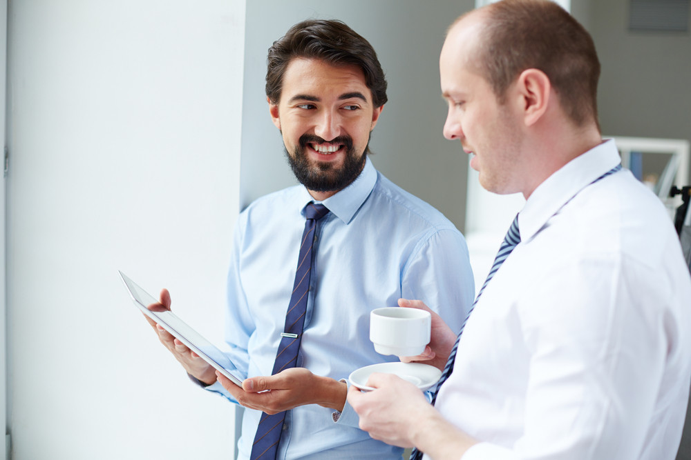 Young businessman with touchpad showing data to his colleague at meeting