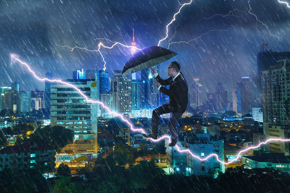 Young businessman with umbrella against thunderstorm. Overcoming challenges and crisis concept. Mixed media