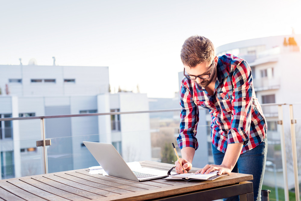 Young businessman working on a laptop computer, standing on the balcony, writing into personal organizer