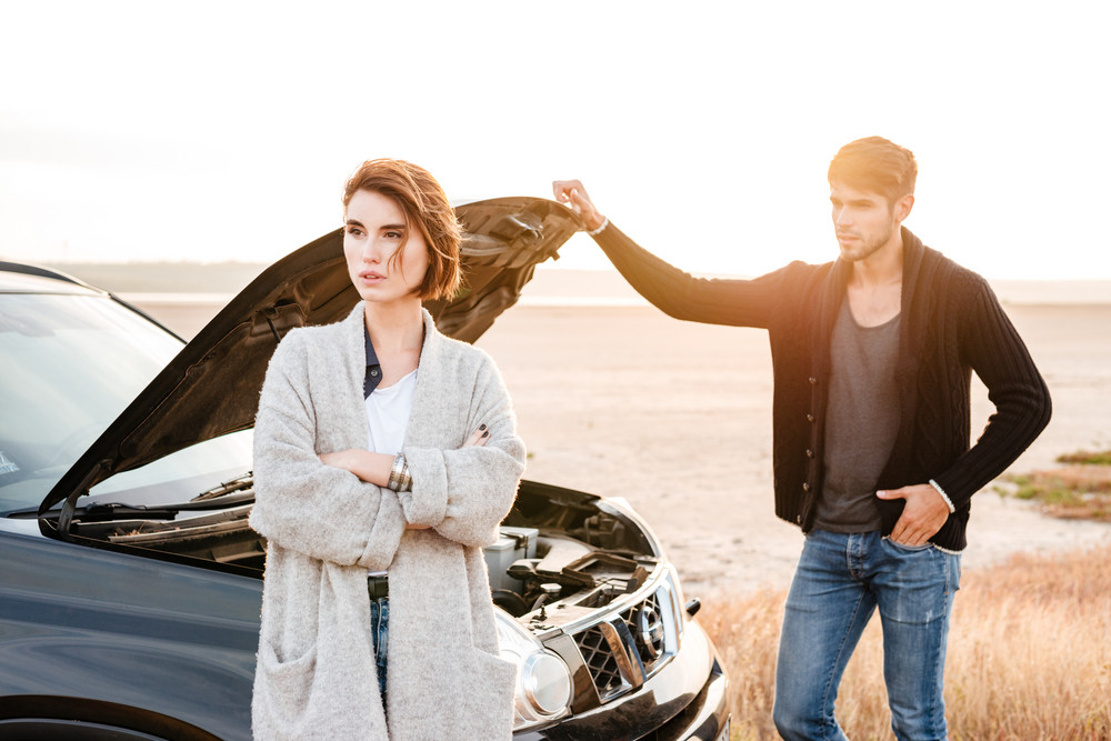 Young casual couple standing near broken car with open hood outdoors