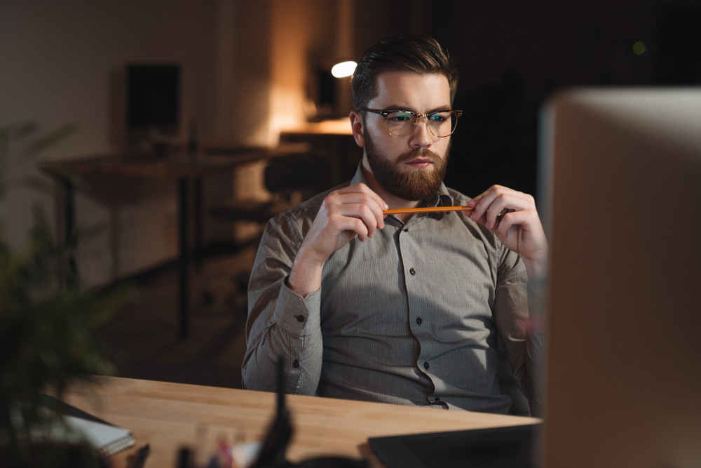 Young concentrated bearded web designer dressed in shirt working late at night and looking at computer. Holding pencil.