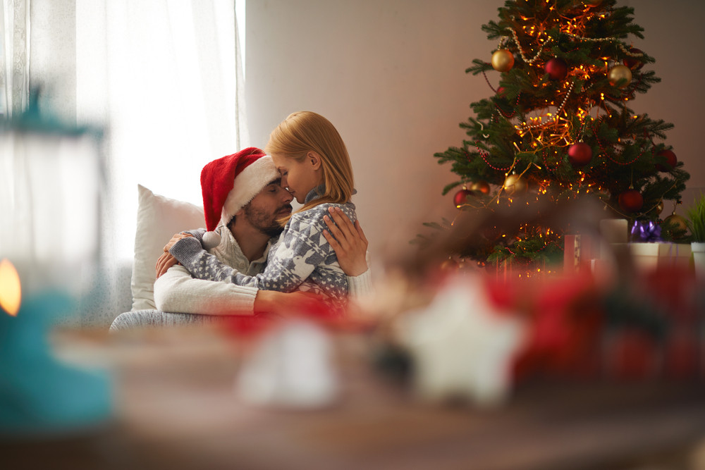 Young couple embracing on Christmas night at home