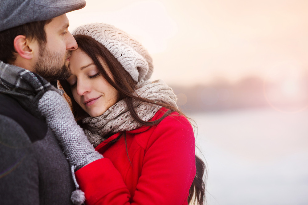 Young couple hugging by the river in winter weather