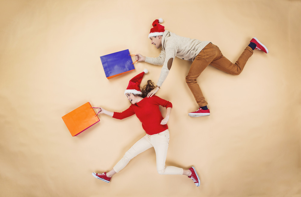 Young couple in Christmas hats having fun running with shopping bags against the beige background