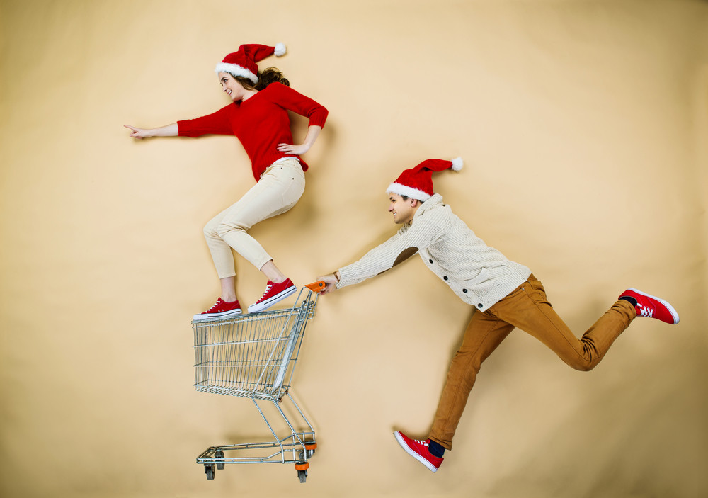 Young couple in Christmas hats having fun running with shopping trolley against the beige background