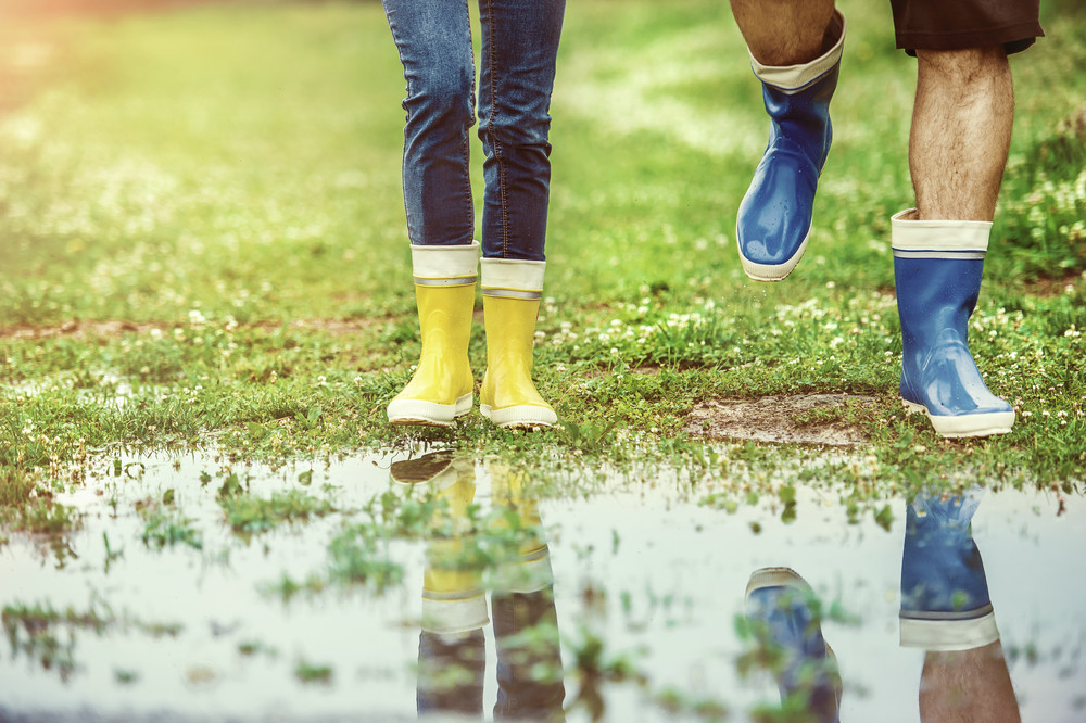 Young couple in colorful wellies walking in muddy nature. Details of feet in puddle