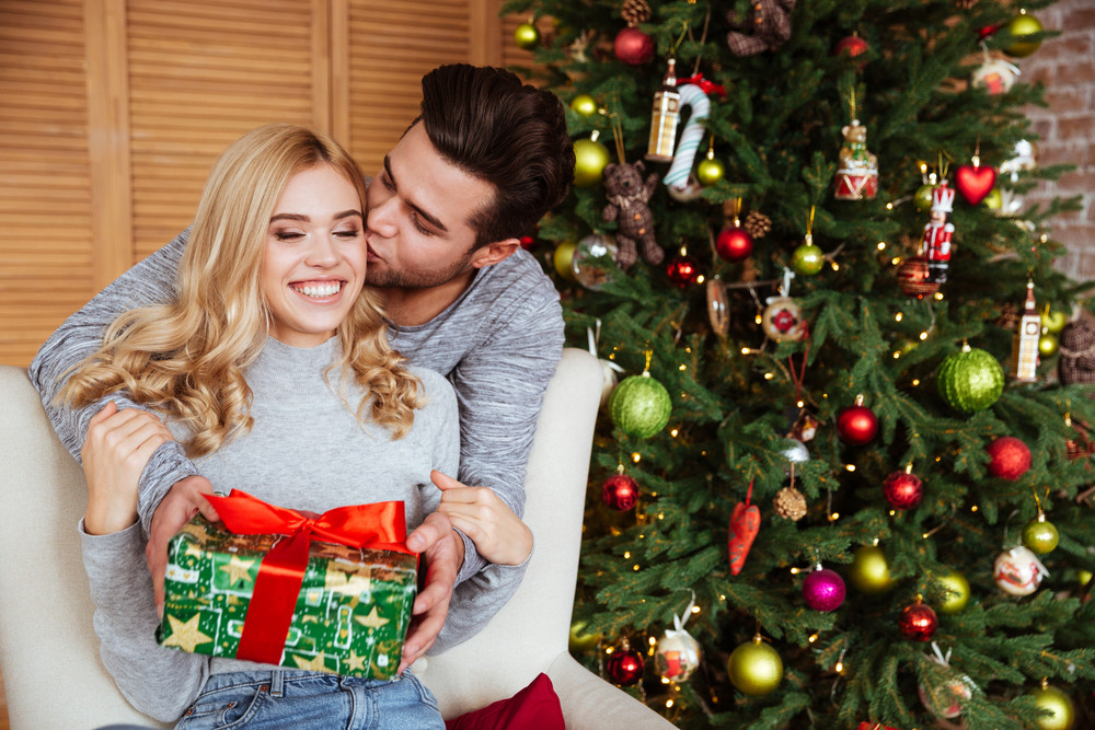 young couple in sweaters with gift near the fir tree girl sitting