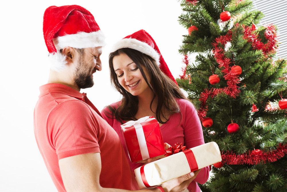 Young couple is dancing close to christmas tree. Woman is pregnant.