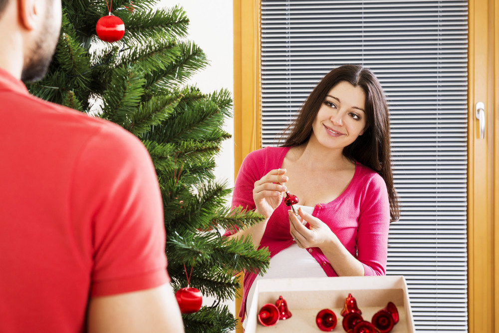 Young couple is decorating christmas tree. Woman is pregnant.