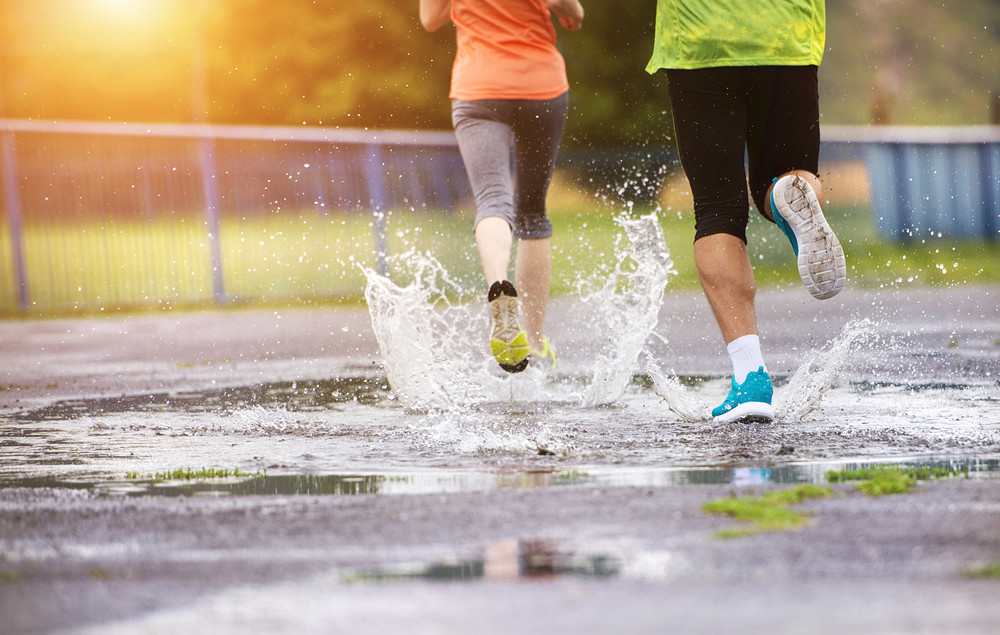 Young couple jogging on asphalt in rainy weather