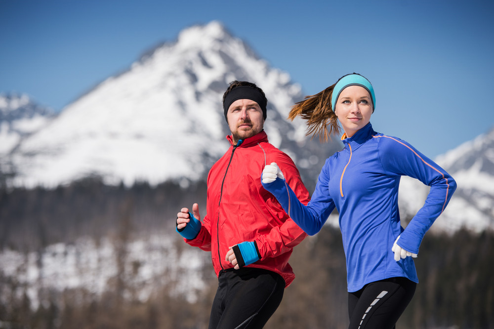 Young couple jogging outside in sunny winter mountains