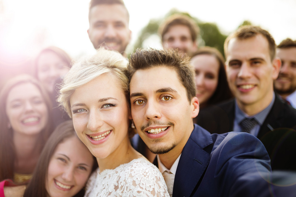 Young couple of newlyweds with group of their firends taking selfie