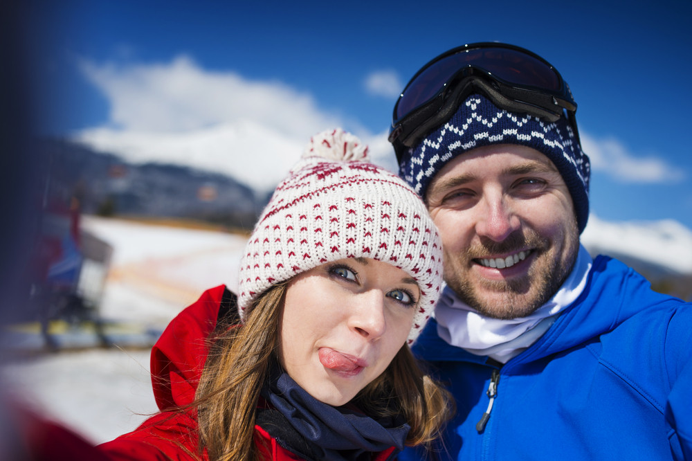 Young couple outside in sunny winter mountains