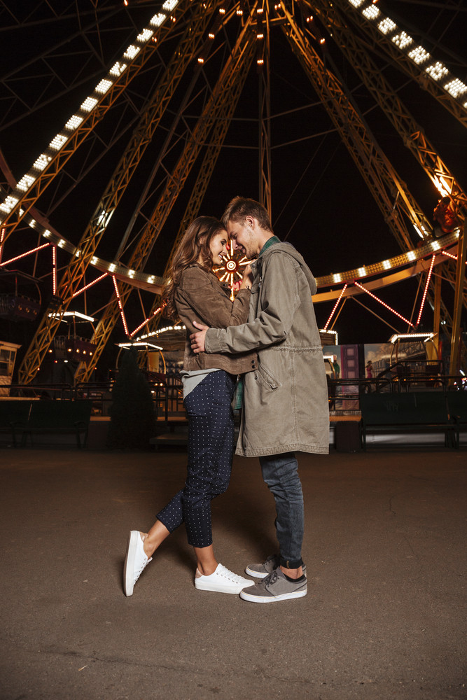 Young couple posing together at an attractions park. in warm clothes. full length