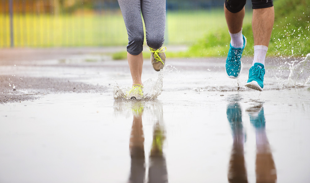 Young couple running on asphalt sports field in rainy weather. Details of legs and sports shoes splashing in puddles.