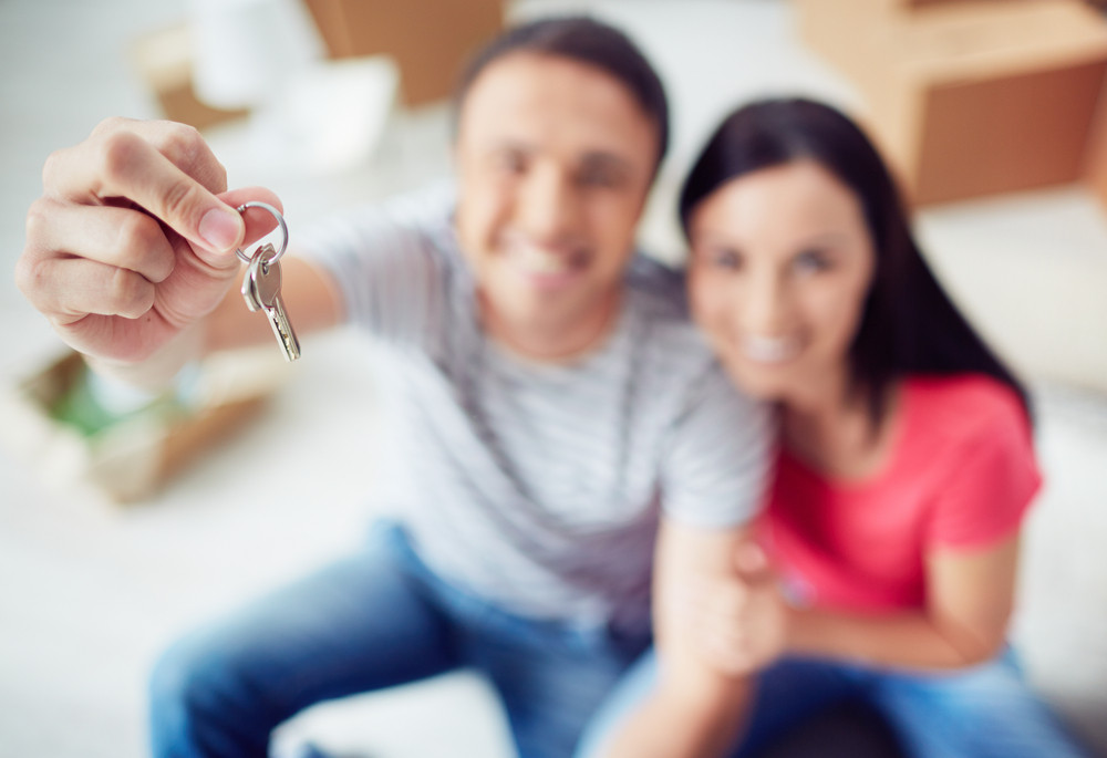 Young couple showing key from new apartment