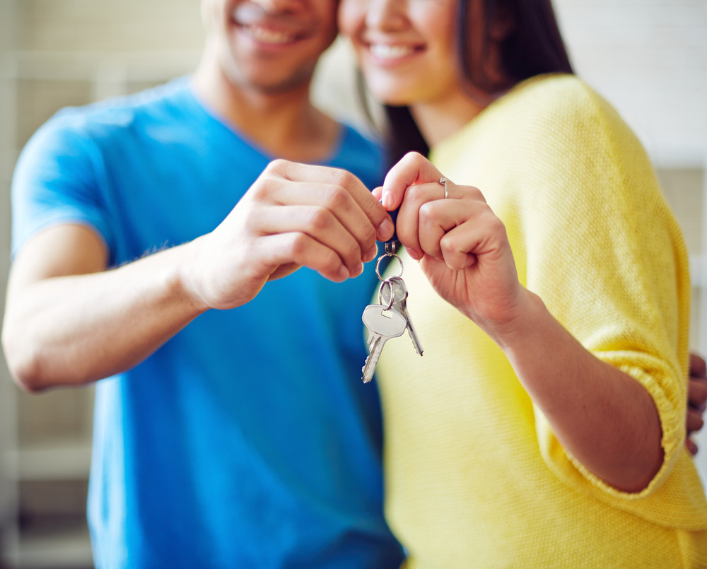 Young couple showing key from new house