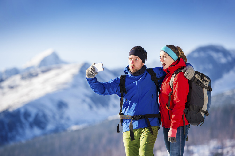 Young couple taking selfie on a hike outside in sunny winter mountains