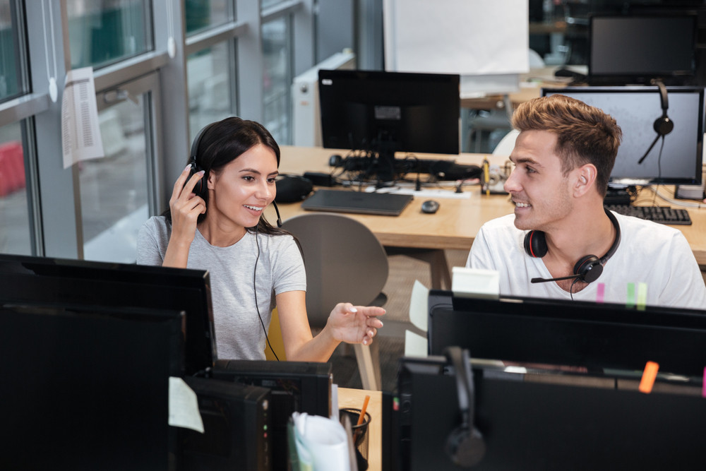 Young Coworkers in white t-shirts sit by the table in headphones in office