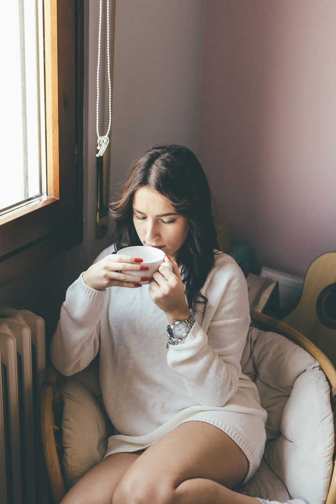 Young eastern woman at home sitting near window relaxing in her living room drinking coffee or tea - relaxing, serene concept