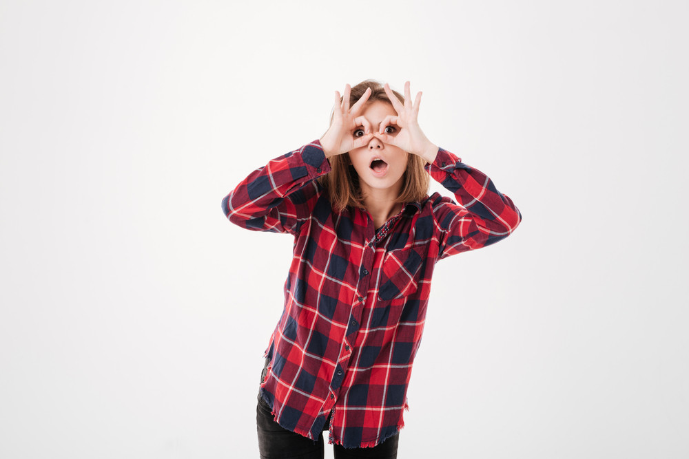 Young excited woman in plaid shirt looking through fingers isolated on the white background