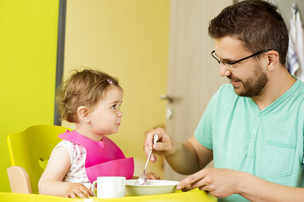 Young father and his little daughter having breakfast together