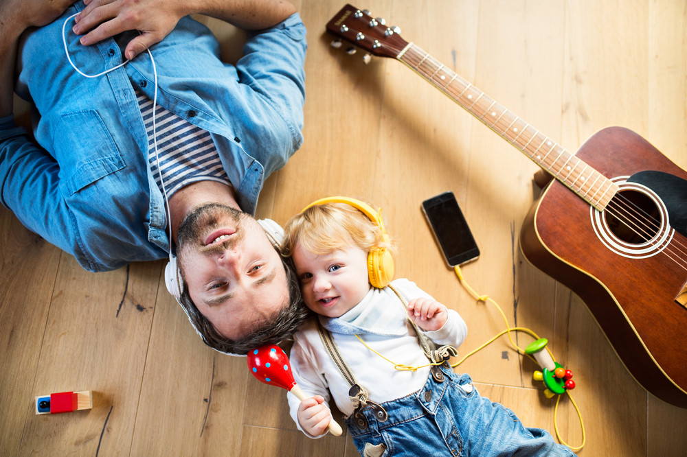 Young father and his little son with smart phone and earphones, listening music at home, lying on wooden floor, guitar and other musical instruments surrounding them.
