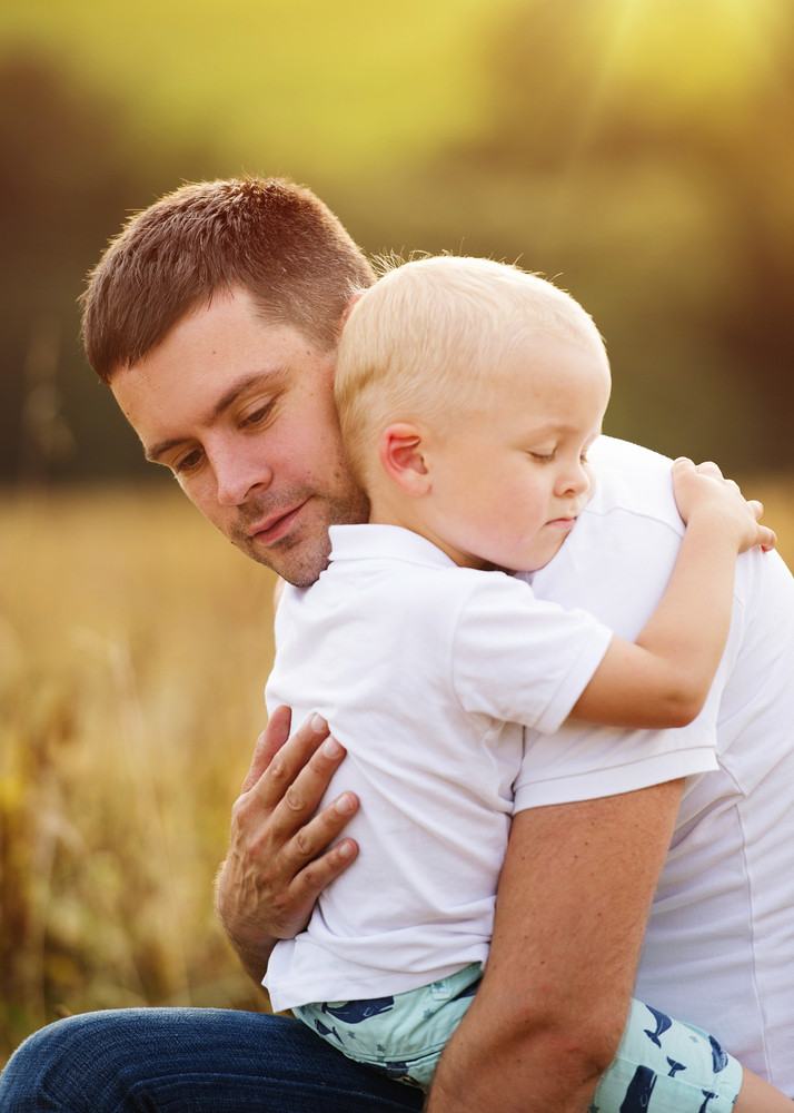 Young father and son enjoying life together. They are hugging outside in nature