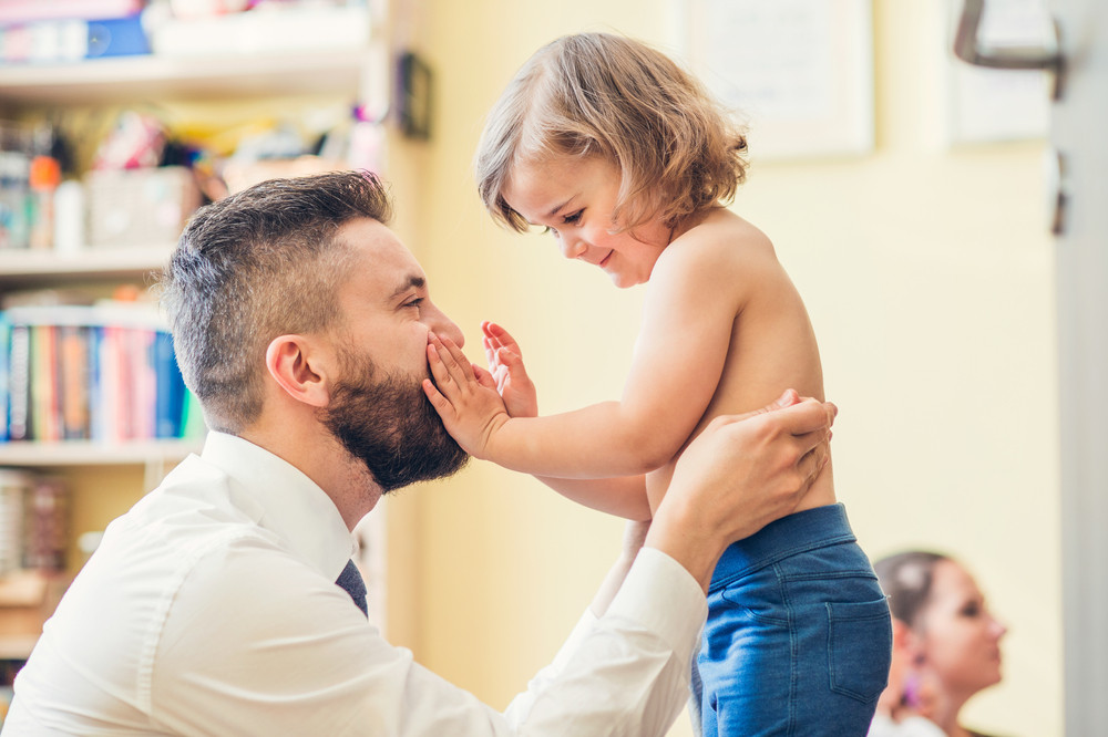 Young father getting his little daughter ready in a morning