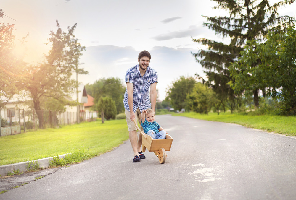 Young father pushing his little son in wooden wheelbarrow on road on sunny day