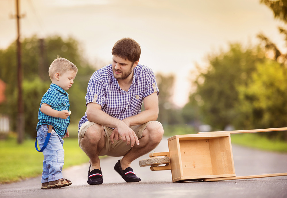 Young father talking with his little son on street