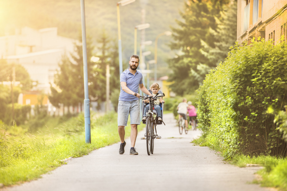 Young father with his little daughter on bicycle in green sunny park