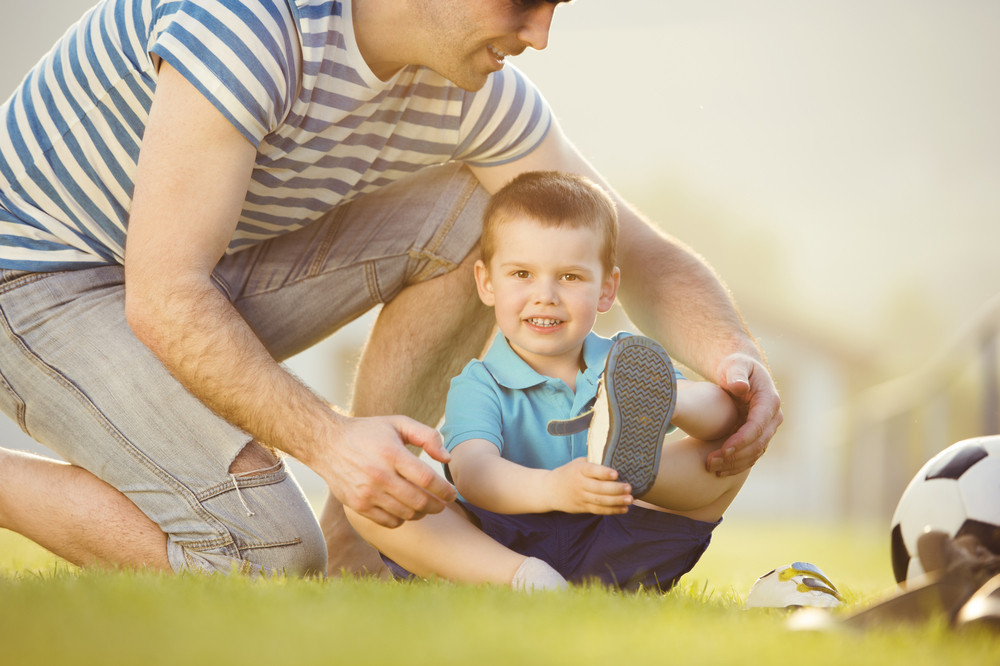 Young father with his little son changing shoes on football pitch