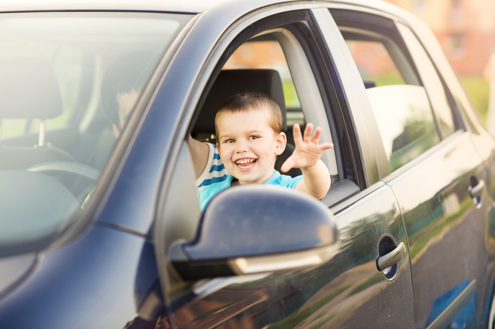 Young father with his little son driving car together